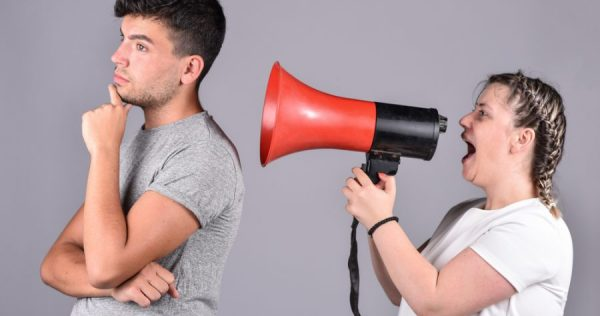 young girl shouting into megaphone at guy who can't hear
